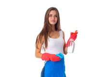 Woman holding duster and detergent. Young pretty woman in white shirt and blue apron with red gloves holding duster and detergent on white background in studio Stock Images