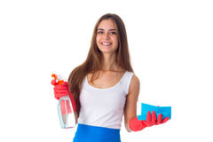 Woman holding duster and detergent. Young smiling woman in white shirt and blue apron with red gloves holding duster and detergent on white background in studio Royalty Free Stock Photos