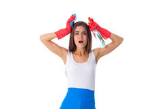 Woman holding duster and detergent. Young womanwith long hair  in white shirt and blue apron with red gloves holding duster and detergent on white background in Royalty Free Stock Image