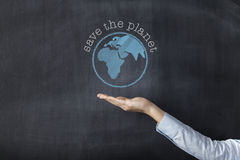 Woman holding earth front of blackboard Stock Image