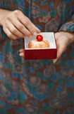 Woman holding eclair in the box Stock Photos