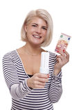 Woman holding an eco-friendly light bulb. With a 10 Euro banknote threaded through it in a conceptual image of efficiency and savings stock photo