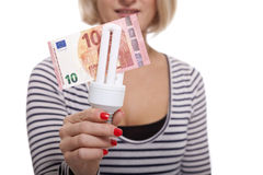 Woman holding an eco-friendly light bulb. With a 10 Euro banknote threaded through it in a conceptual image of efficiency and savings royalty free stock photos