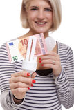 Woman holding an eco-friendly light bulb. With a 10 Euro banknote threaded through it in a conceptual image of efficiency and savings royalty free stock photography