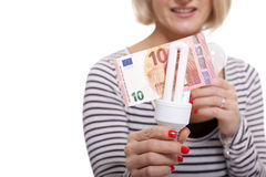 Woman holding an eco-friendly light bulb. With a 10 Euro banknote threaded through it in a conceptual image of efficiency and savings stock image