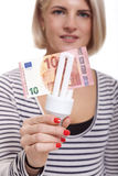 Woman holding an eco-friendly light bulb. With a 10 Euro banknote threaded through it in a conceptual image of efficiency and savings royalty free stock images