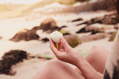 Woman holding an egg in her hand on the beach Royalty Free Stock Photography