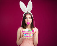 Woman holding egg with her lips over pink backgrround Stock Image