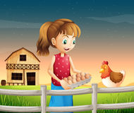 A woman holding an eggtray with eggs near the fence Stock Image