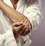 Woman holding elbow in pain. Closeup of woman holding elbow in pain Royalty Free Stock Photos