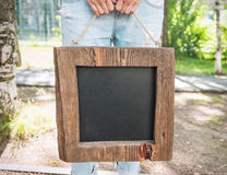 Woman holding empty chalkboard with wooden frame. Template Mock. Woman holding empty chalkboard with wooden frame outdoor. Template Mock up Royalty Free Stock Image