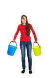 Woman holding empty plastic buckets. Royalty Free Stock Photo