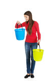 Woman holding empty plastic buckets. Royalty Free Stock Image