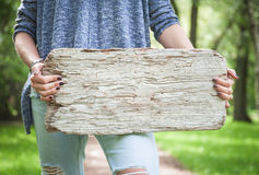 Woman holding empty wooden board. Template mock up Stock Images