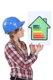 Woman holding energy-rating poster. In the shape of a house royalty free stock photography