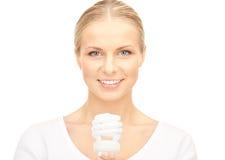 Woman holding energy saving bulb Stock Photos