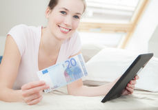 Woman holding 20 euro and tablet Royalty Free Stock Photos