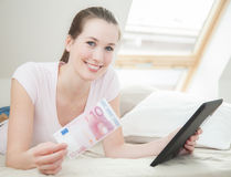 Woman holding 10 euro and tablet device Royalty Free Stock Photos