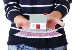 Woman holding euros bills and house model . Stock Photography