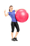 Woman holding an exercise ball and giving a thumb up Stock Photo