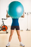 Woman holding exercise ball in health club Stock Photography