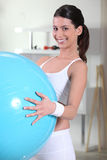 Woman holding an exercise ball Stock Photography