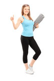 Woman holding exercise mat and giving thumb up Stock Photo