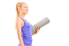 Woman holding an exercise mat and looking up Stock Image