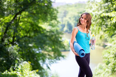 Woman holding exercise mat and water bottle in parkland. Royalty Free Stock Photography