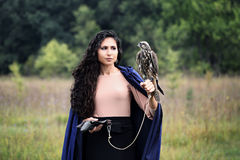 Woman holding a falcon. Woman in a blue hooded cloak holding a falcon on his arm stock photo