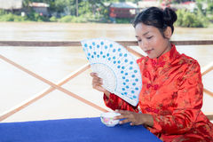Woman holding fan and cup Royalty Free Stock Image
