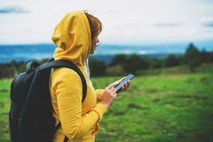 Woman holding in female hands gadget technology, tourist young girl on background green grass using mobile smartphone, hiker. Texting finger message on screen royalty free stock image