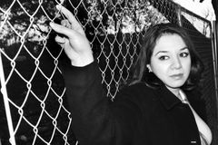 Woman holding a fence. Woman holding herself on a fence Royalty Free Stock Images