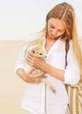 Woman holding fennec fox in her hands during traveling in Sahara. Young woman holding fennec fox in her hands during traveling in Sahara Stock Photos