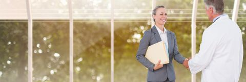 Woman holding files and folders handshake with doctor with blurred background. Digital composite of Woman holding files and folders handshake with doctor with Stock Image