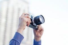 Woman holding film camera taking photo of city Stock Image