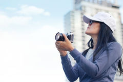 Woman holding film camera taking photograph in the city. Background Stock Photo