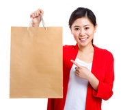 Woman holding and finger pointing to shopping bag Royalty Free Stock Photography