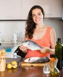 Woman holding fish at kitchen Stock Photos
