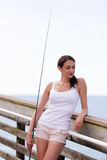 Woman holding a fishing pole and leaning on a rail Royalty Free Stock Image