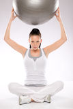 Woman holding fitness ball above her head Royalty Free Stock Photography