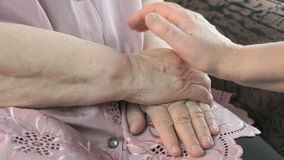 Woman holding flabby wrinkled hands of aged woman. Woman holding the flabby wrinkled hands of an aged woman. Woman soothes the old woman in times of stress stock video