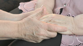 Woman holding flabby wrinkled hands of aged woman. Woman holding the flabby wrinkled hands of an aged woman. She soothes the old woman in times of stress. Close stock video