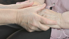 Woman holding flabby wrinkled hands of old woman. Woman holding the flabby wrinkled hands of an old woman. Woman soothes the old woman in times of stress stock video footage