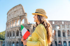 Woman holding flag looking into distance at Colosseum in Rome Royalty Free Stock Photo