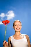 Woman holding flower against blue sky Stock Photos