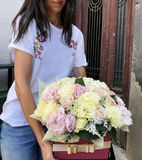 Woman Holding Flower Box of White Hydrangea ,Pink Peonies and Roses stock photo