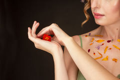 A woman is holding a flower in the palm of her hand. Stock Photography