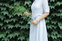 Woman Holding Flowers Near Green Leafed Plants stock image