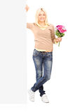 Woman holding flowers next to a blank panel Stock Images